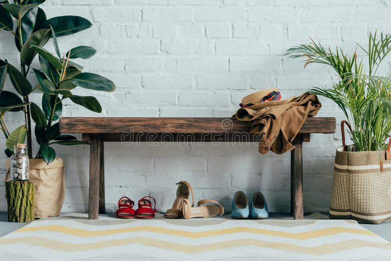 different shoes under wooden bench in corridor at home potted palm tree and ficus royalty free stock photo