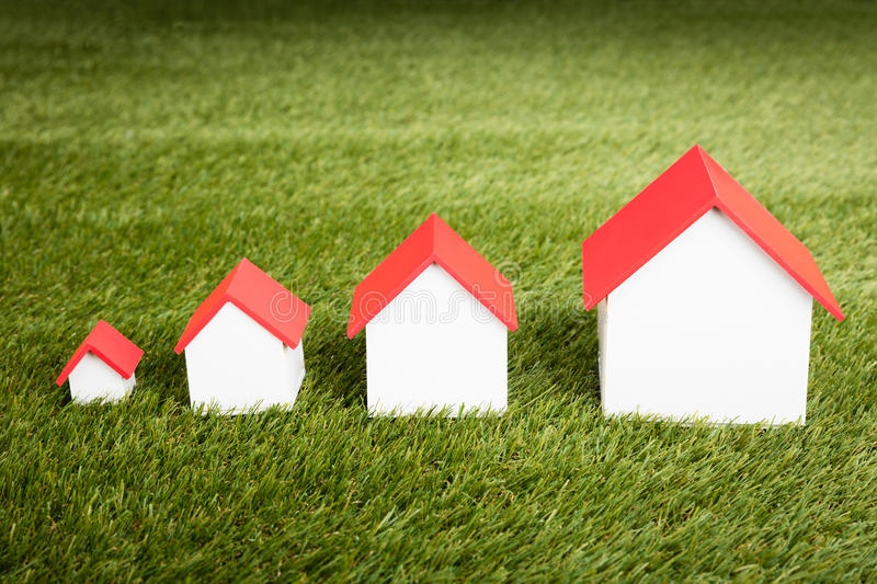Different Size Of Houses In Row. Different Size Of Houses Arranged In Row On Grassy Field royalty free stock photos