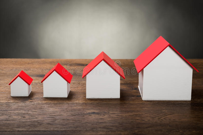 Different Size Houses. In Row On Wooden Table stock photography