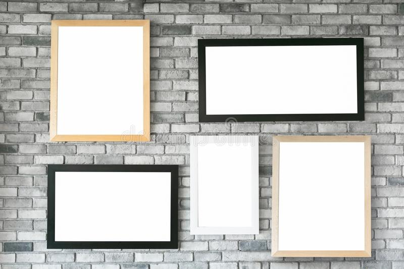 Different size and style empty photo frames on white concrete wa stock photo