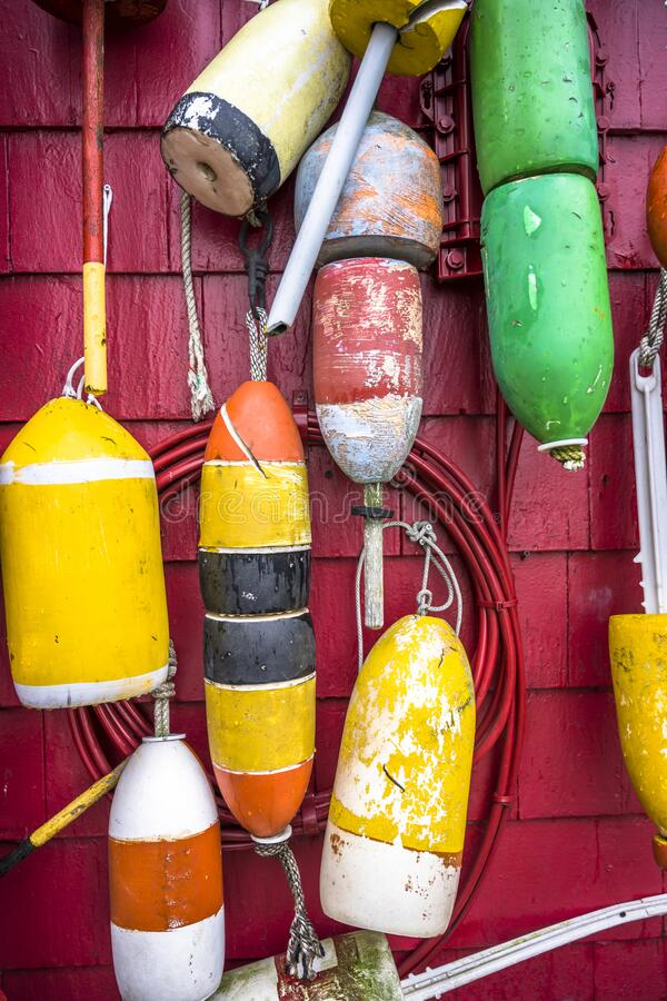 Various outboard used floats for mooring boats and schooners are decoratively hung on the painted wooden wall of the building. Different sized board side floats stock photo