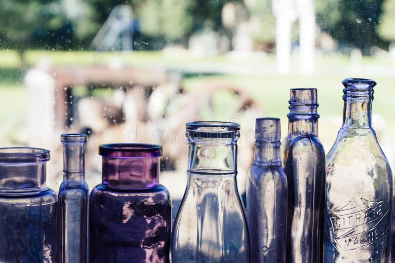 Different sized glass bottles in a row with blurred background royalty free stock photos