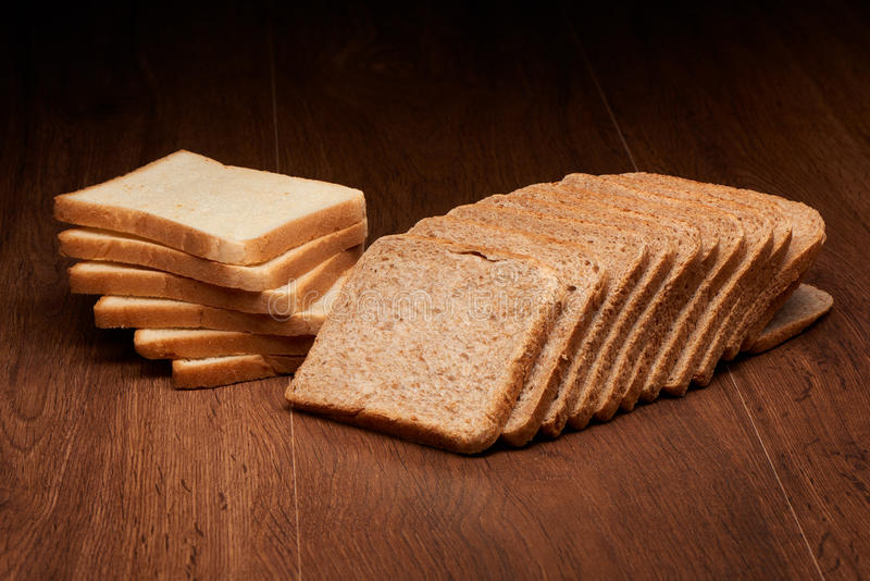 Different sliced bread on dark wooden table stock photography