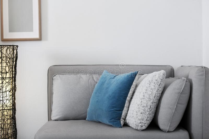 Different soft pillows on sofa in room royalty free stock photos