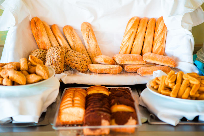 Different sorts of bread on breakfast in cafe. Various buffet sweet bakeries in a hotel restaurant stock photography