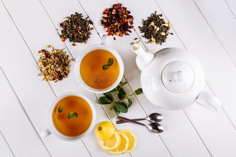 Different sorts of dry tea on white wooden background and two cups and pot. Top view decorated with mint and lemon stock photo