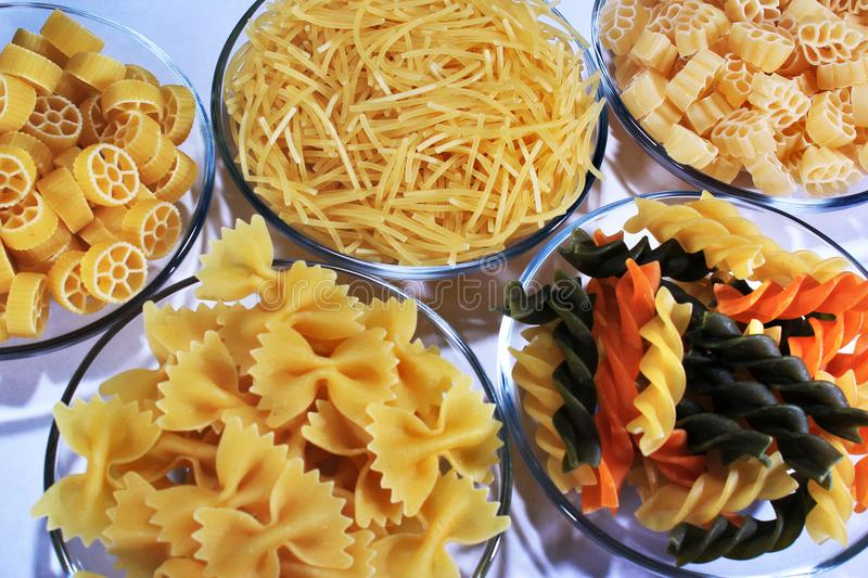Different sorts of pasta in glass bowls.  stock image