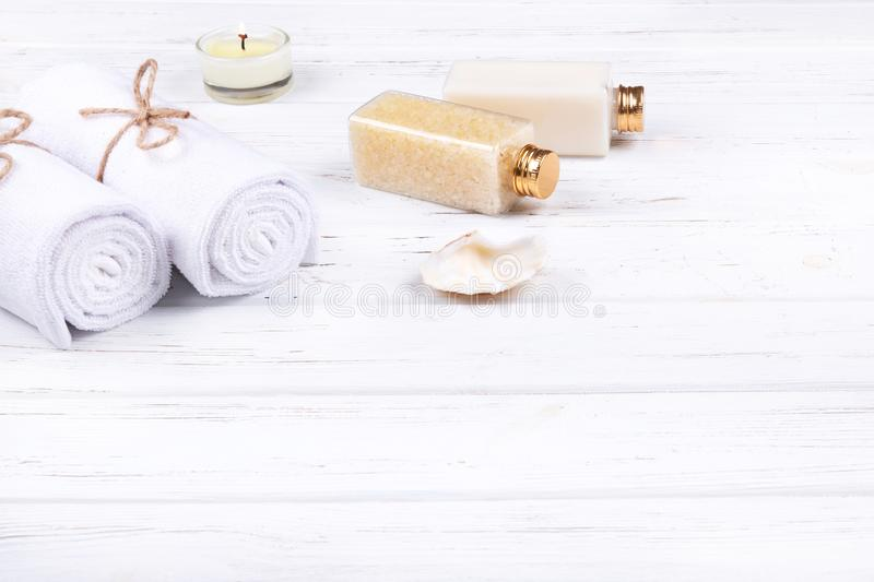 Spa, beauty and wellness products: cream, sea salt, towels, decorated with sea shell and candle with copy space. Different spa, beauty and wellness products royalty free stock photography