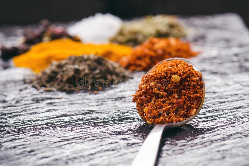 Different spices and herbs on a black slate. Iron spoon with chili pepper. Indian spices. Ingredients for cooking. Healthy eating royalty free stock image