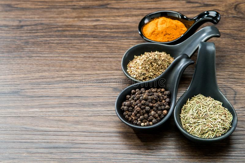 Different spices and herbs in spoons or bowls on a brown wooden background . Food and cuisine ingredients with copy space .Dried. Rosemary,black pepper,red stock photography