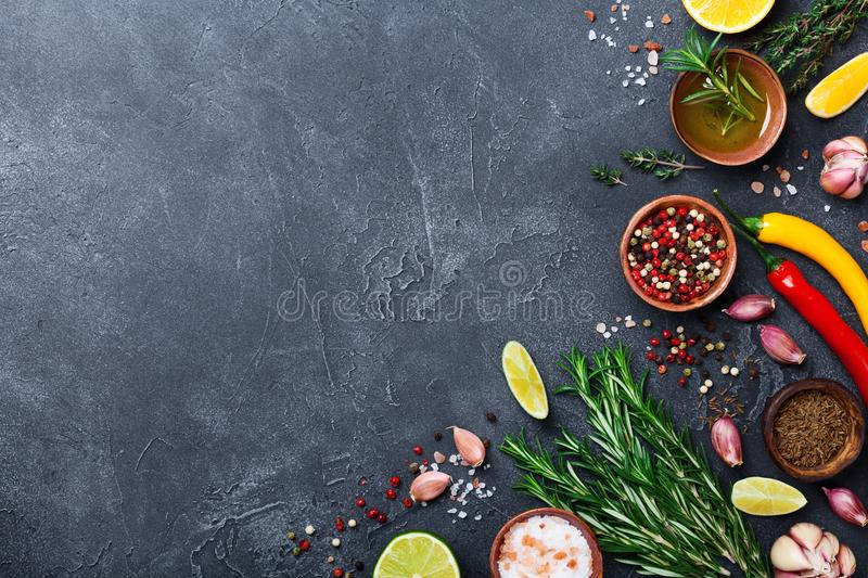 Different spices and herbs on black stone table top view. Ingredients for cooking. Food background. royalty free stock images