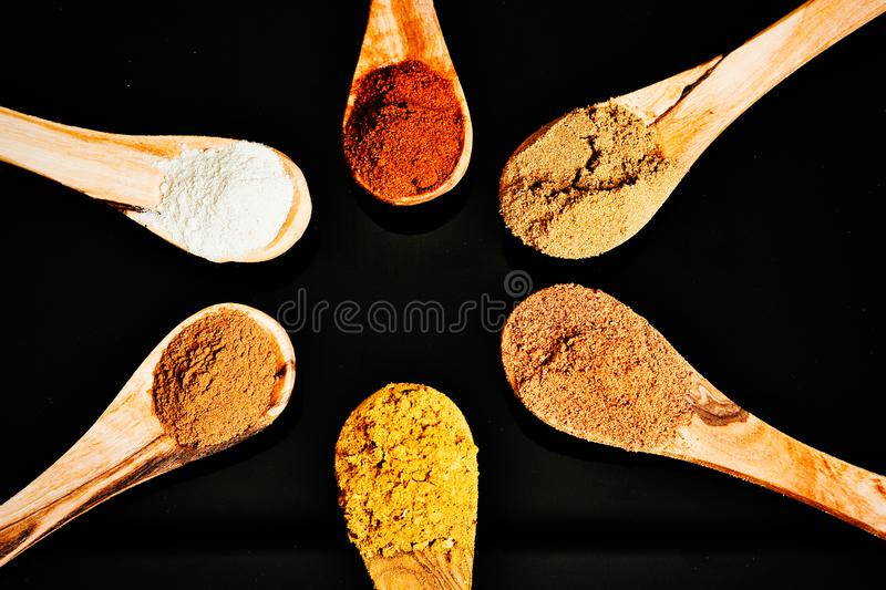 Different spices on olive wood spoons royalty free stock image
