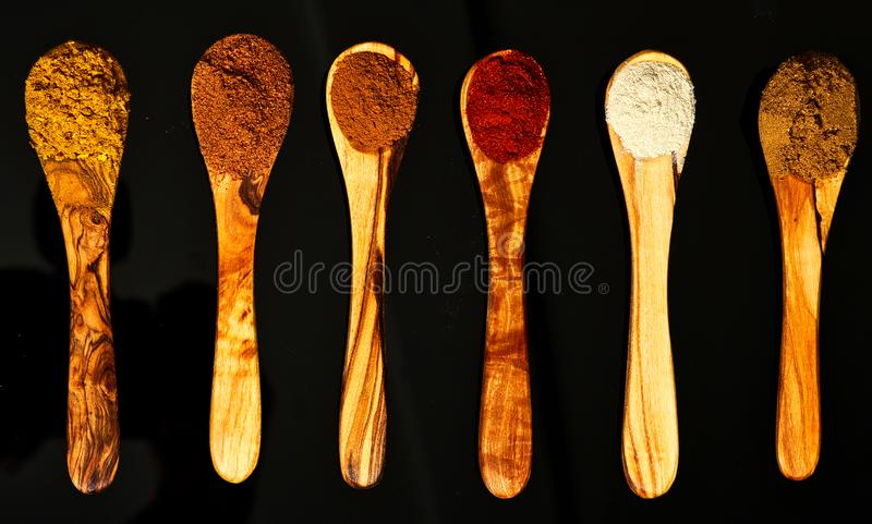 Different spices on olive wood spoons stock photo