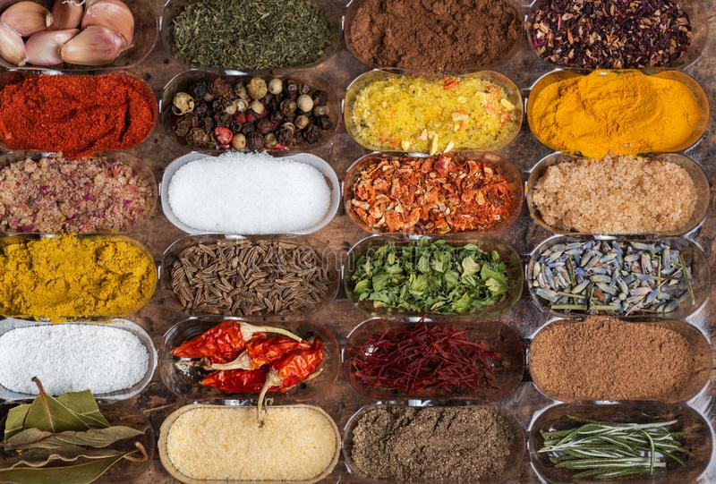 different spices in small containers stock images