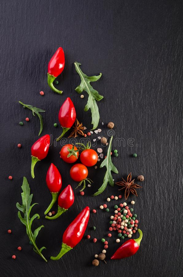 Different spices with tomato and  peppers on black background. Different spices with tomato and  peppers on a black background royalty free stock photos