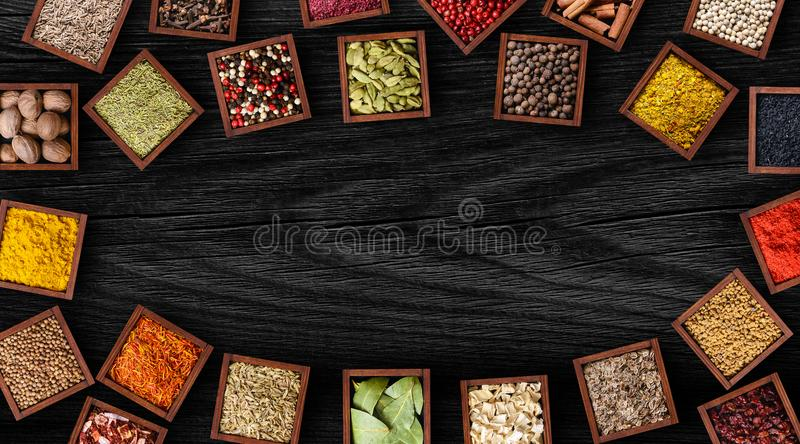Different spices in wooden boxes on black wooden table stock photography