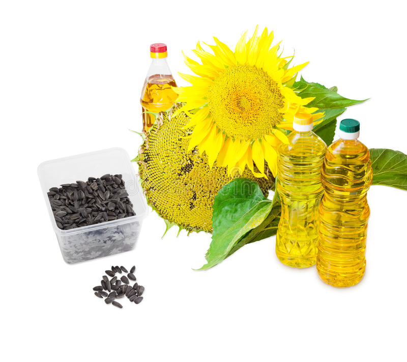 Different sunflower oil, sunflower seeds and flowers of sunflower. Several plastic bottles of sunflower oil of different variety, sunflower seeds in the husk stock images