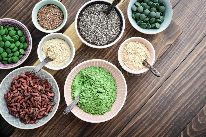 Different super foods in bowls. On a wooden background, top view stock image