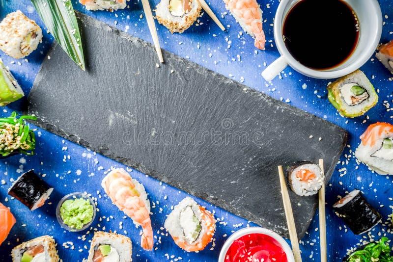 Different sushi mixed set. Assorted sushi set on stone or concrete background.  Japanese classic sushi, sushi nigiri. rolls, soy sauce, ginger, chopsticks. Top stock image