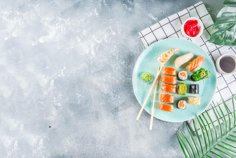 Different sushi mixed set. Assorted sushi set on stone or concrete background.  Japanese classic sushi, sushi nigiri. rolls, soy sauce, ginger, chopsticks. Top stock photography