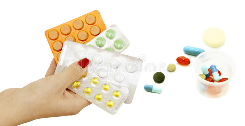 Different tablets in hands and on a white background. Different pills in different colors for the treatment in the hands and on a white background stock photography