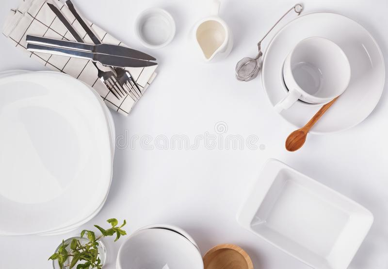 Different tableware and dishes on the white background, top view. royalty free stock photo