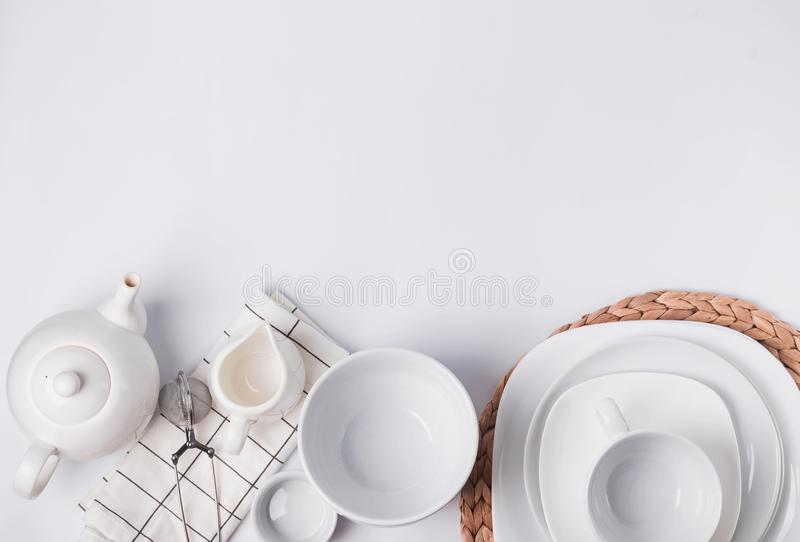 Different tableware and dishes on the white background, top view. stock photo
