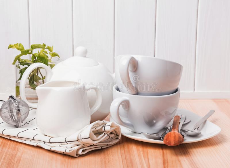 Different tableware, plates, cups standing near the white wooden wall royalty free stock photo