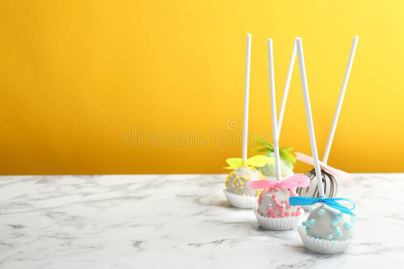 Different tasty cake pops on white marble table against yellow background. Space for text royalty free stock images