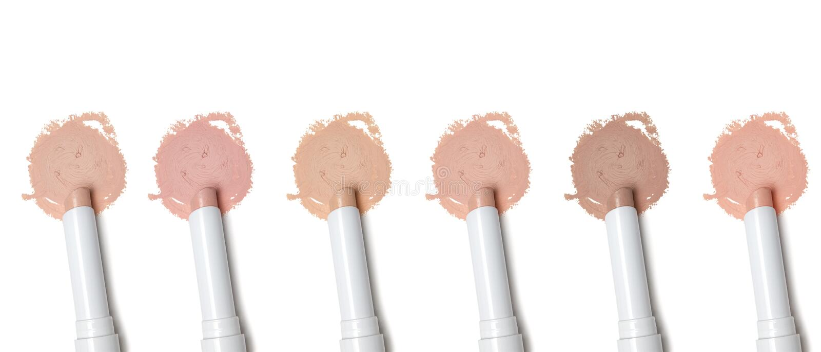 Different tones of concealer. Different tones of makeup concealer pencil on white background royalty free stock images
