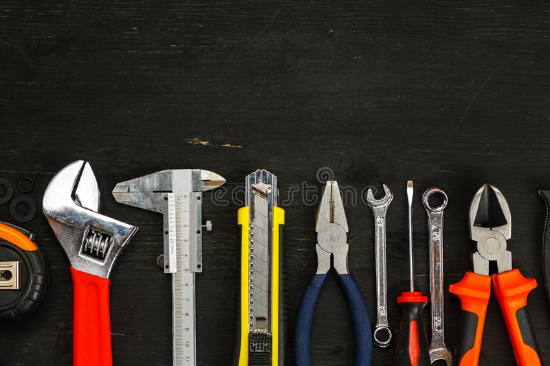 Different tools on a black wooden background, top view, space for text stock image