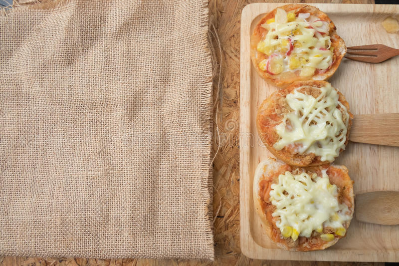 Different topped mini pizza buns. On wooden tray royalty free stock photos