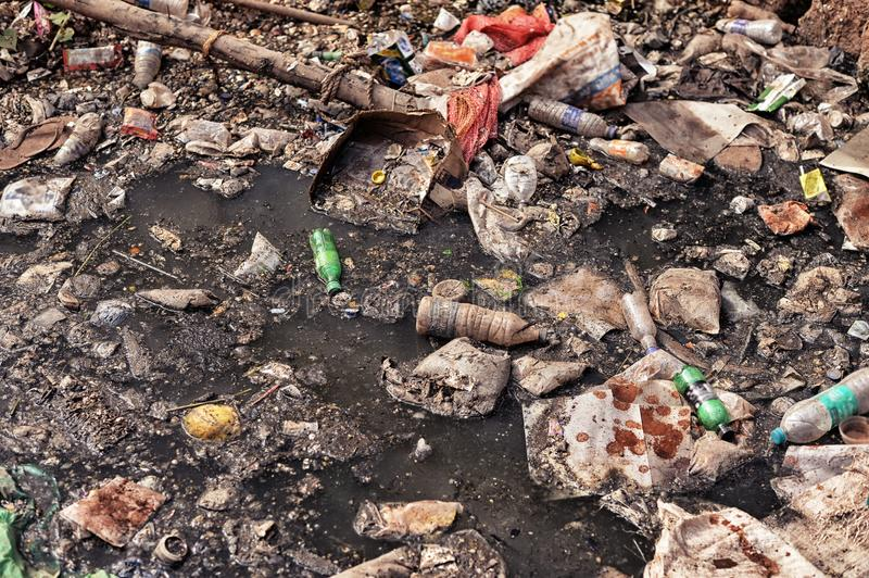 Trash on wet ground. Different trash lying on wet ground close up royalty free stock image