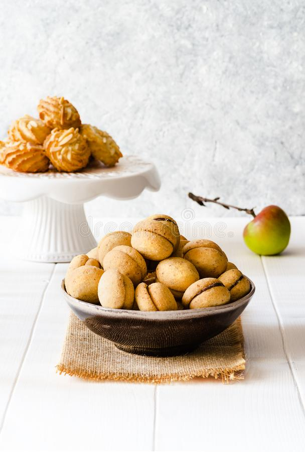 Different type of delicious cookies and a apple on white wooden. Delicious cookies and a apple on on white wooden table stock images
