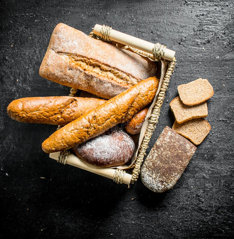 Different types of bread in the basket. On black rustic background stock image