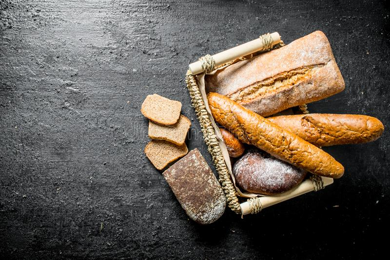 Different types of bread in the basket. On black rustic background stock images