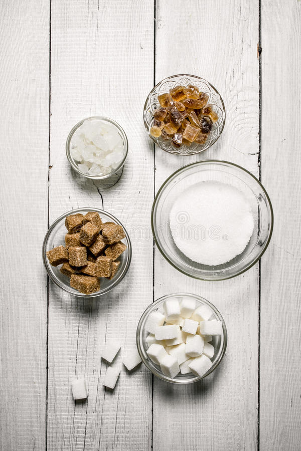 Different types of brown and white sugar in the cups. stock image