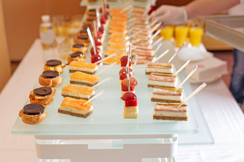 Different types of canapes on buffet table stock images