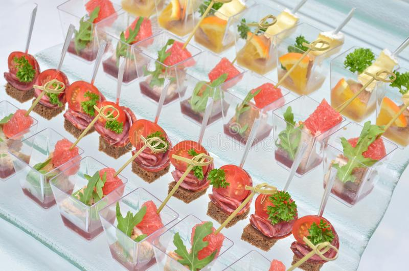 Different types of canapes in transparent glasses and wooden skewers on a glass step support on a banquet, top view royalty free stock images