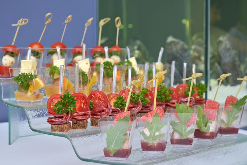Different types of canapes in transparent glasses and wooden skewers on a glass step support on blue background and tank royalty free stock photo
