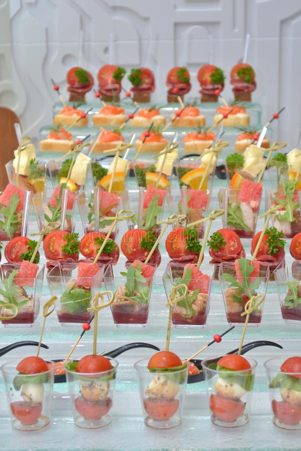 Different types of canapes in transparent glasses and wooden skewers on a glass support on banquet, vertically oriented royalty free stock photo