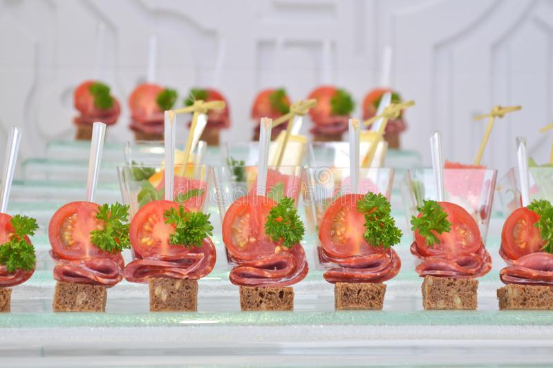 Different types of canapes with transparent and wooden skewers on a glass step support on a banquet, macro stock photos