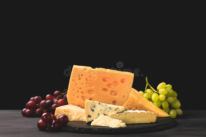 Different types of cheese on board with grapes on black royalty free stock photos