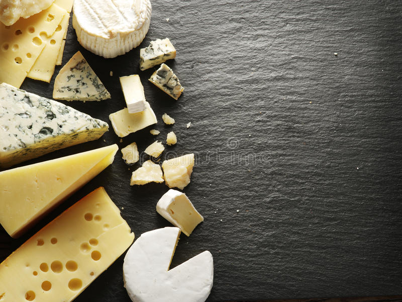 Different types of cheeses. Different types of cheeses on black board royalty free stock photography