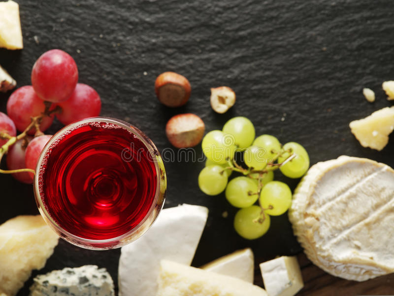 Different types of cheeses with wine glass and fruits. Top view royalty free stock photography
