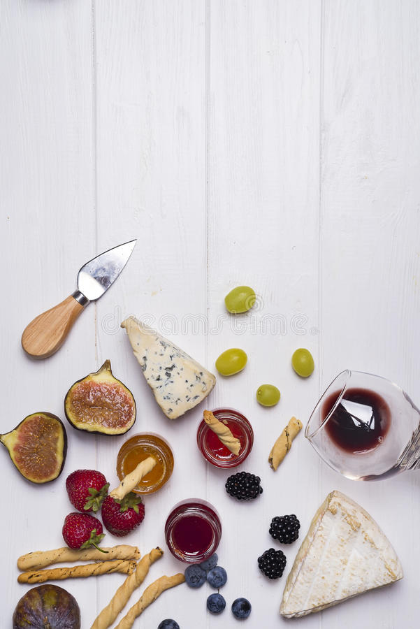 Different types of cheeses with wine glass and fruits royalty free stock images
