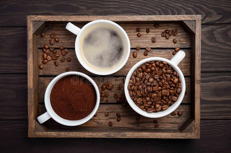 Different types of coffee - ground, grain and beverage on dark wooden background royalty free stock photos