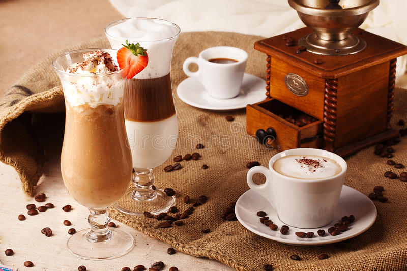 Different types of coffee whipped cream strawberries still life with grinder beans royalty free stock photo