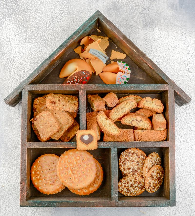 Different types of cookies: cereal, kantuchini, Chinese and puff, in a wooden box in the shape of a house. Different types of cookies: cereal, cantuccini stock photos