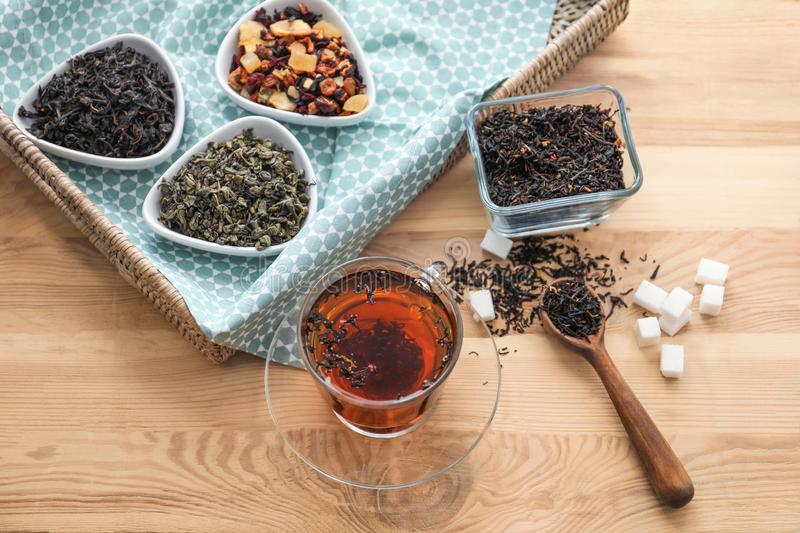 Different types of dry tea leaves and cup of aromatic beverage on wooden table stock images